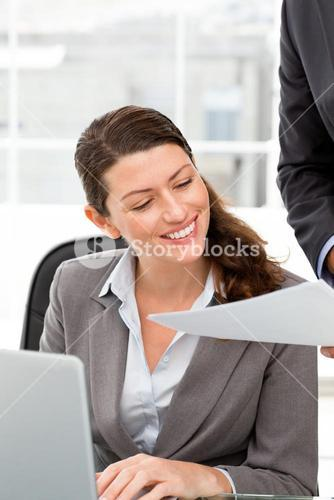 Happy businesswoman reading a paper while working with a laptop
