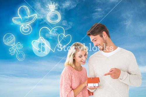 Composite image of attractive couple holding miniature house model
