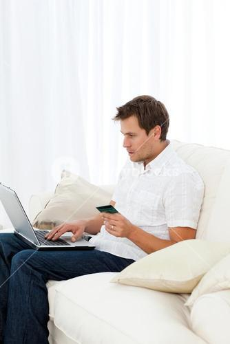 Positive man buying online sitting on his sofa