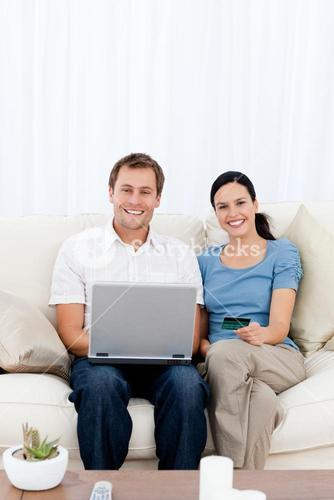 Portrait of a happy couple buying online with their credit card