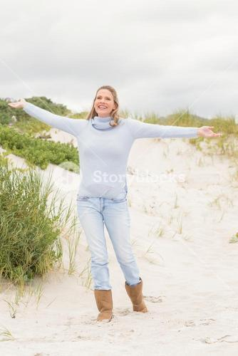Smiling woman standing with open arms