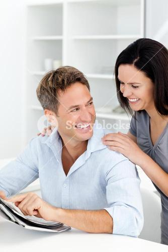Happy man showing something on the newspaper to his girlfriend