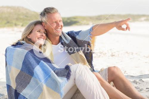 Happy couple wrapped up in blanket