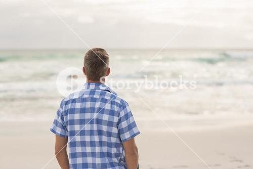 Casual man looking out to sea