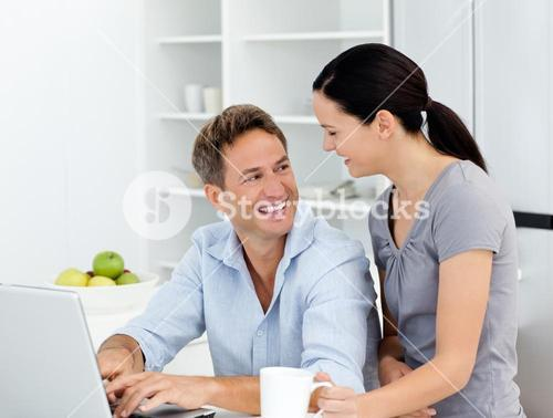Happy couple working with a laptop in the kitchen