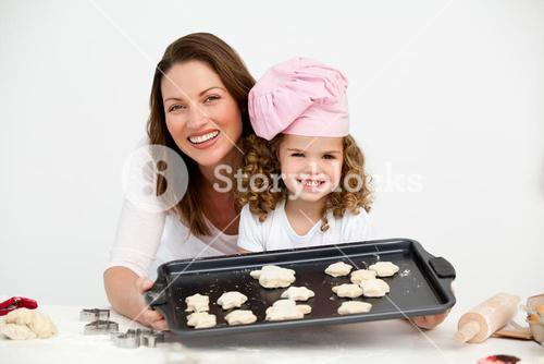 Happy mother and daughter showing a plate with biscuits
