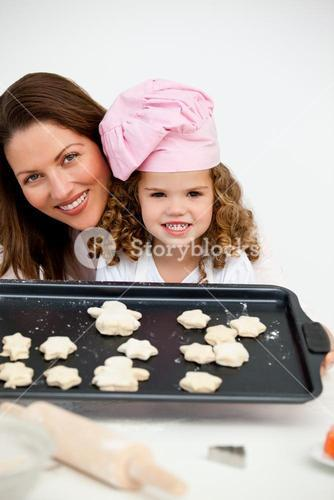 Happy mother and daughter holding a plate with biscuits