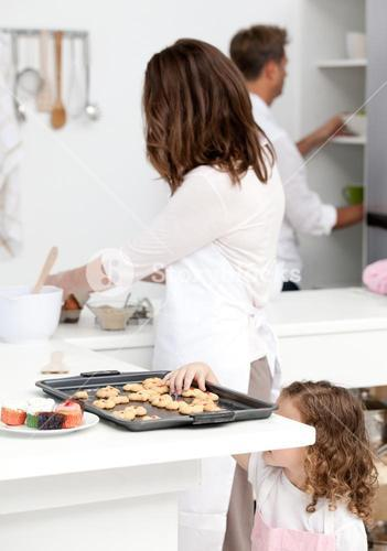 Cute little girl taking cookies while her parents are cooking