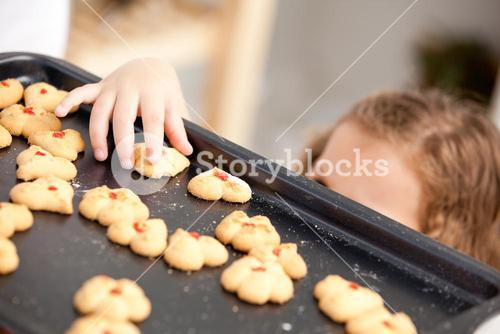 Close up of a little girl taking a cookie behind her mother