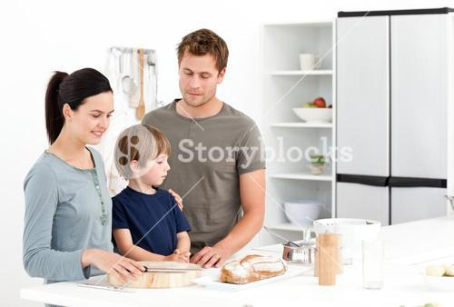 Happy family eating bread in the kitchen