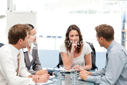 Charismatic businesswoman at a table with her team