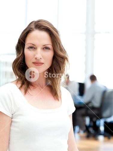 Confident businesswoman standing in front of her team while working