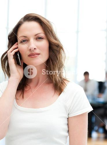 Confident businesswoman on the phone while her team is working
