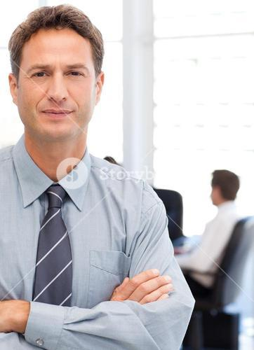 Assertive businessman standing in front of his team while working at a table