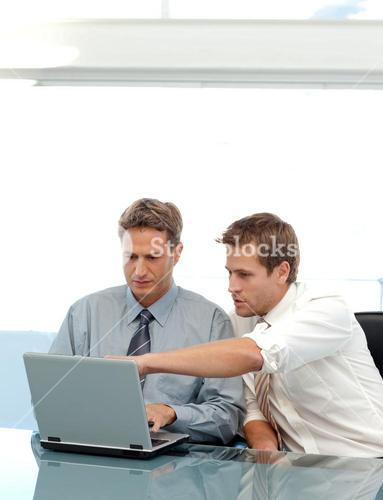 Two partners working together with a laptop sitting at a table