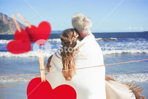 Composite image of couple wrapped up in blanket on the beach looking out to sea