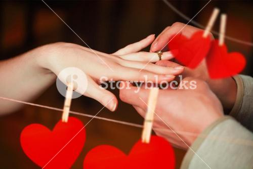 Composite image of close up on man putting on ring during marriage proposal
