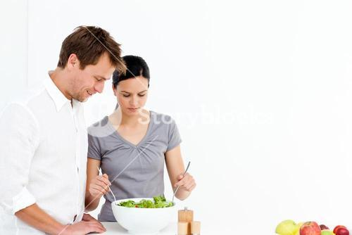 Active couple preparing a salad for lunch