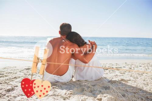 Composite image of couple sitting on the sand watching the sea