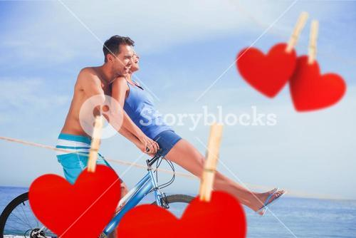Composite image of man giving girlfriend a lift on his crossbar