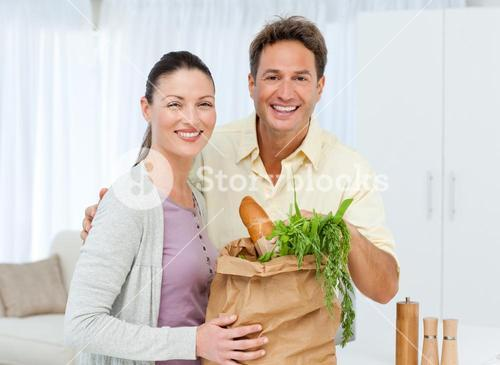 Portrait of a couple coming back from the market with vegetables