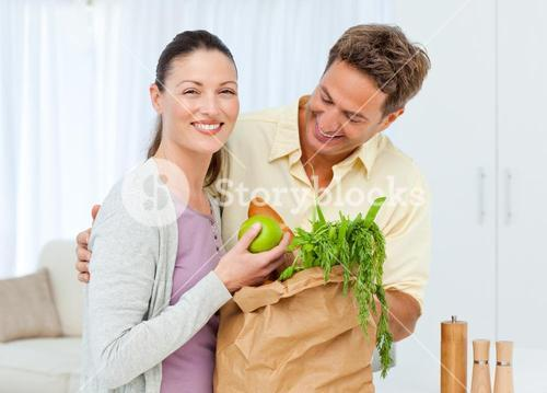 Happy couple coming back from the market with fruit, vegetables and bread