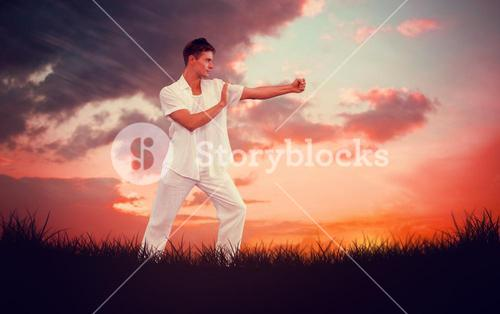 Composite image of handsome man in white doing tai chi