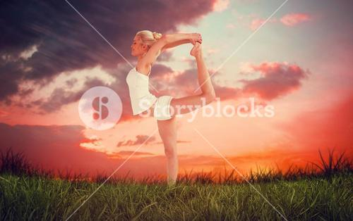 Composite image of sporty woman stretching body while balancing on one leg