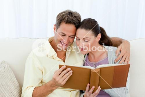 Attentive man and woman looking at a photo album on the sofa
