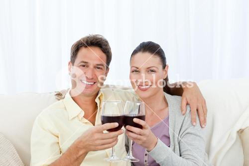 Portrait of a couple clinking glasses of red wine on the sofa
