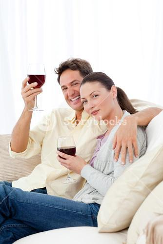 Happy couple enjoying their glasses of red wine on the sofa