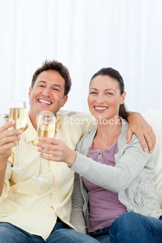 Happy couple celebrating with flute of champagne