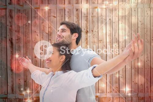Composite image of cute couple standing with arms out
