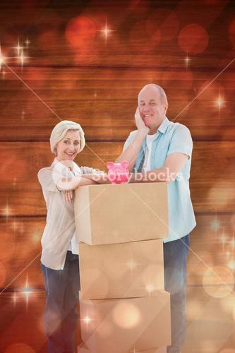 Composite image of older couple smiling at camera with moving boxes and piggy bank