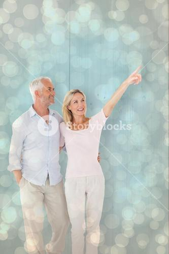 Composite image of smiling couple walking and pointing