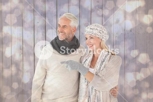 Composite image of happy couple in winter fashion looking