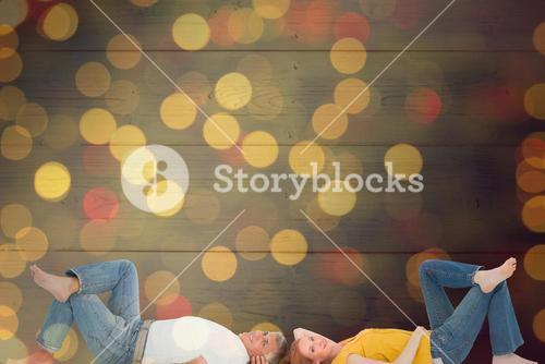 Composite image of casual couple lying on floor