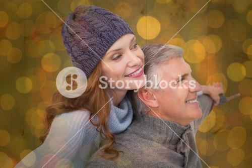 Composite image of carefree couple in warm clothing