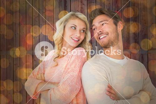 Composite image of attractive couple smiling with arms crossed