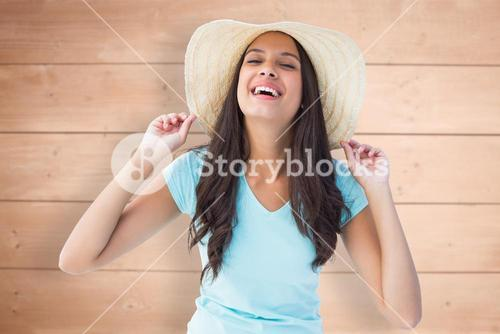 Composite image of happy young brunette wearing sunhat
