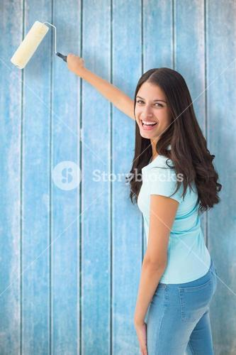 Composite image of happy young brunette painting with roller