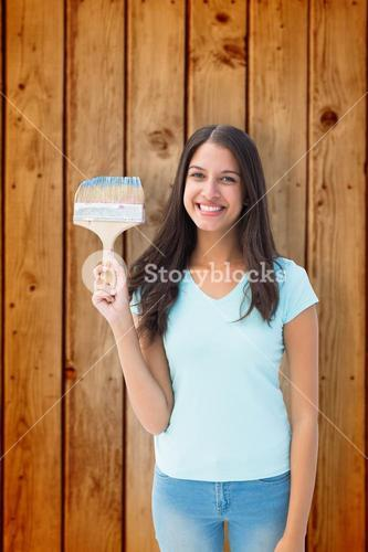 Composite image of happy young brunette holding paintbrush