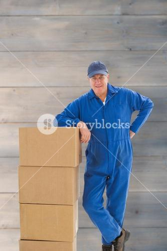 Composite image of happy delivery man leaning on pile of cardboard boxes