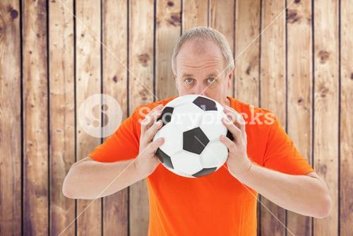 Composite image of nervous football fan holding ball