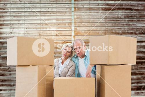 Composite image of stressed older couple with moving boxes