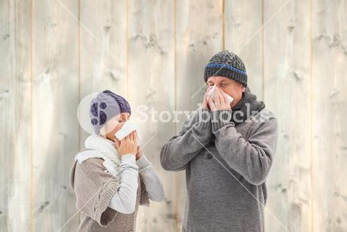Composite image of sick mature couple blowing their noses