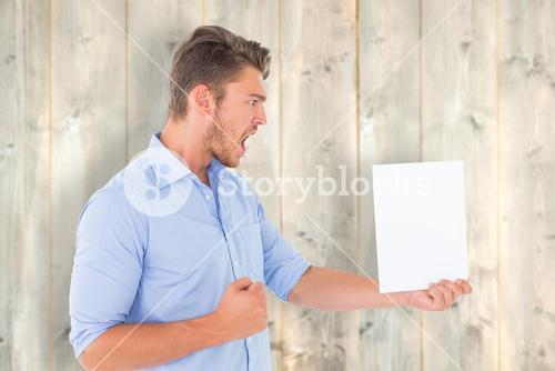 Composite image of angry man looking at page