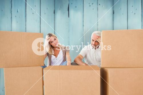 Composite image of stressed couple looking at moving boxes