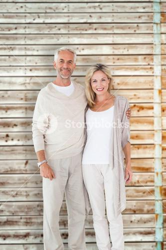 Composite image of happy couple smiling at camera together