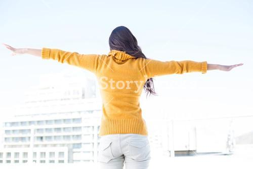 Woman looking camera with arms raised on